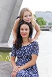 Embracing mother and daughter near fountain. In summer time stock photo