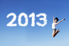 Embracing new year 2013 by jumping. Woman jumping under clear blue sky with 2013 clouds next to her Stock Images