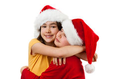 Embracing Santa Claus kids. Kids wearing Santa Claus hats isolated on white Royalty Free Stock Photography