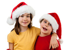 Embracing Santa Claus kids. Kids wearing Santa Claus hats isolated on white Stock Photography