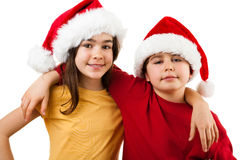 Embracing Santa Claus kids. Kids wearing Santa Claus hats isolated on white Stock Images