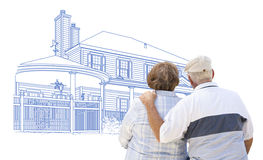 Embracing Senior Couple Looking At House Drawing on White. Curious Embracing Senior Couple Looking At House Drawing on White royalty free stock images