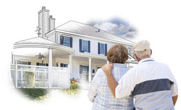 Embracing Senior Couple Over House Drawing and Photo on White royalty free stock photo