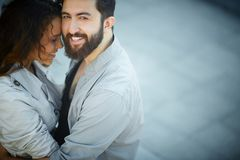 Embracing sweetheart. Image of happy men looking at camera while embracing his sweetheart Stock Image