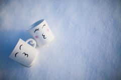 Embracing two mugs with a picture in the snow Stock Photography