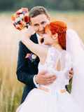 Embracing on wheat field at sunny day. Beautiful redhair bride with handsome groom enjoy the honeymoon Stock Photos