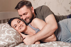 Embracing young couple lying in the bed. Royalty Free Stock Images