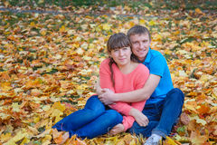 Embracing young couple sitting in a park on yellow leaves in aut Stock Image