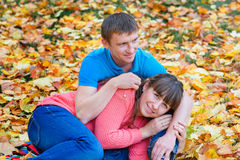Embracing young couple sitting in a park on yellow leaves in aut Royalty Free Stock Photos