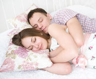 Embracing young couple sleeping. On the bed Stock Images