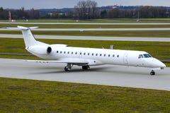 Embraer 145 flygplan på en taxiway Royaltyfri Fotografi