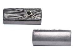 Embrague de plata con una broche en un fondo blanco foto de archivo libre de regalías