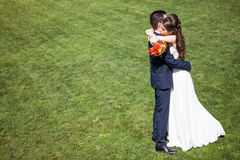 embrancing丈夫的婚礼礼服的妻子 免版税图库摄影