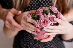 Embrassant des roses de prise d'homme et de femme ensemble Images libres de droits