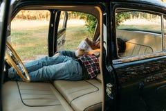 embrassant les personnes qui se situent la voiture et en tenant des mains regardez par la fenêtre dans la voiture Vue de côté hab Images libres de droits