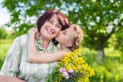 Embrasse la grand-mère de petite-fille Photo stock
