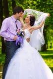 Embrassement de jeunes mariés Images stock