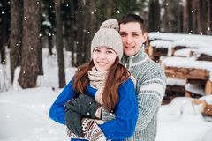 Embrassement des couples regardant l'appareil-photo avec des sourires en parc d'hiver photo stock