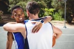 Embrassement heureux de joueurs de basket Images libres de droits