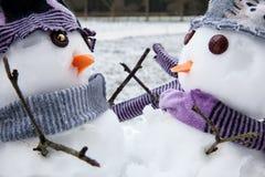 Embrassement mignon de deux amis de bonhommes de neige Photographie stock