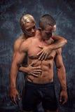 Embrassement musculaire de couples Photo stock