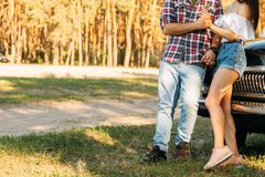 embrassez Amour et affection entre un jeune couple au parc, près de la vieille voiture un type dans un avion de plaid et des jean photos stock