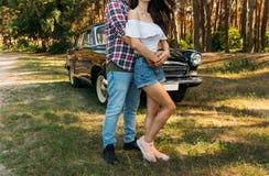 embrassez Amour et affection entre un jeune couple au parc, près de la vieille voiture un type dans un avion de plaid et des jean Photographie stock