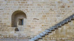 An embrasure and a staircase on the stone wall of an ancient for. Tress stock photos
