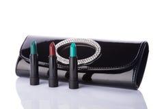 Embrayage de sac à main et ensemble noirs de rouges à lèvres à la mode Photographie stock