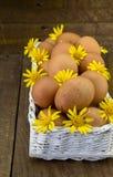 Embrayage des oeufs dans le panier blanc avec les marguerites jaunes Photographie stock