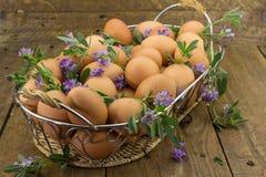 Embrayage des oeufs et des fleurs dans un panier sur le banc en bois rugueux Photographie stock libre de droits