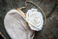 A embreagem das mulheres com a rosa do branco na bandeja de bronze com um ornamento Fotos de Stock