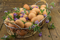 Embreagem dos ovos e das flores em uma cesta no banco de madeira áspero Fotografia de Stock Royalty Free