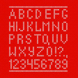 Embroided by cross stitch english alphabet with numbers and symbols on red cloth texture. Stock Images