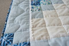 Embroidered by dark blue and white patterns a scrappy blanket 29. Blanket made manually from fabric slices Stock Photo