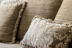 Embroidered elegant cushion in a couch. An elegant brown embroidered cushion around normal cushions with yarn edgings, all of them over a couch royalty free stock images