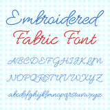 Embroidered fabric font with calligraphic letters. Vector thread alphabet Stock Image