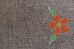 Embroidered flower over the linen background. Flower through the canvas of jute Stock Photo