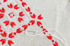 Embroidered fragment on flax by red and white cotton threads. Macro embroidery texture flat stitch. Stock Photo