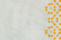 Embroidered fragment on flax by yellow and white cotton threads. Macro embroidery texture flat stitch. Royalty Free Stock Photos