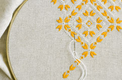 Embroidered fragment on flax by yellow and white cotton threads. Macro embroidery texture flat stitch. Stock Photos