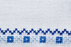 Embroidered fragment on white flax. Cross stitch. Stock Photo