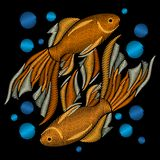 Embroidered goldfish. Embroidery with golden fish on a black bac Royalty Free Stock Photo