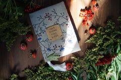 The embroidered handwork notebook among hips, plants and flowers Royalty Free Stock Images