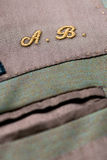 Embroidered initials on clothing. With the letters A sand B in gold thread above a pocket, detail of the texture of the cloth Stock Photos