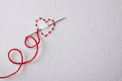 Embroidered red heart on a white cloth top view Stock Image