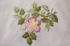 Embroidered satin stitch pink flower on cotton cloth Stock Photography