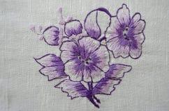 Embroidered satin stitch purple floweron cotton cloth Stock Image