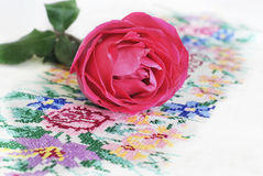 Embroidered tablecloth and flower rose. Colored embroidered tablecloth and flower rose on it on a white background Royalty Free Stock Image