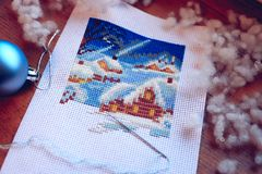 Embroidered winer and snowman. Winter cross stitch. Work in progress. Stock Photography